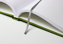 Hardcover book in green linen, lying open, with bookmark ribbon